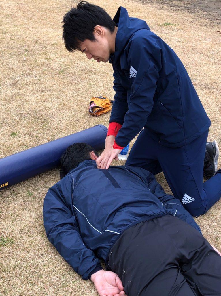 グラウンドでスポーツ選手の治療